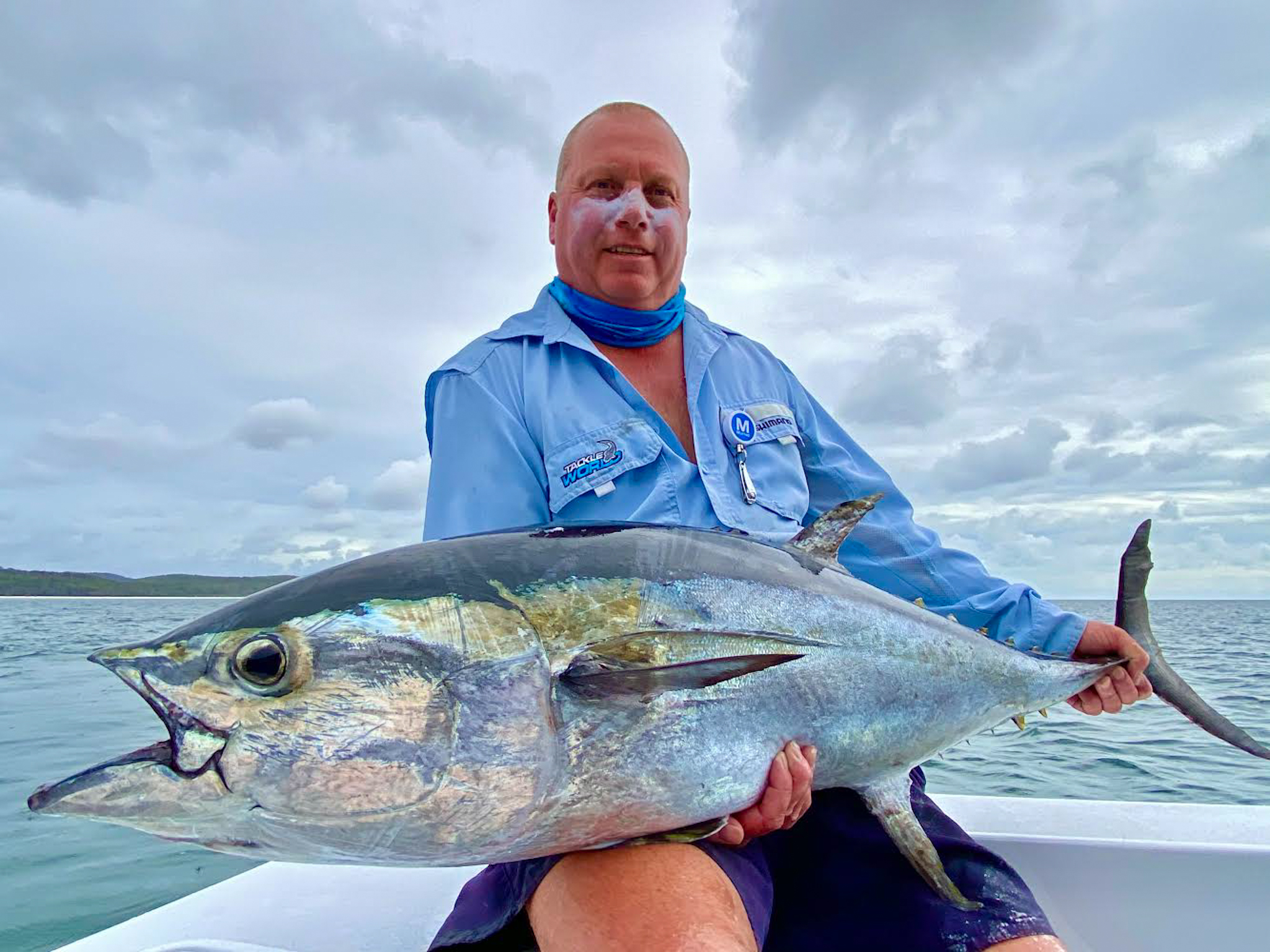 man holding a large red fish on a fishing charter in hervey bay, queensland, australia